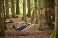 Person relaxing on a hammock in the Queen Elizabeth Forest Park whilst visiting the Lodge Forest  Visitor Centre in Aberfoyle.